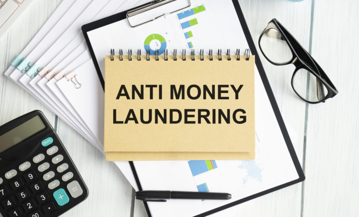 Paper with text AML Anti Money Laundering on a table